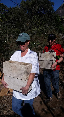 Carrie and Adam carrying cinderblocks